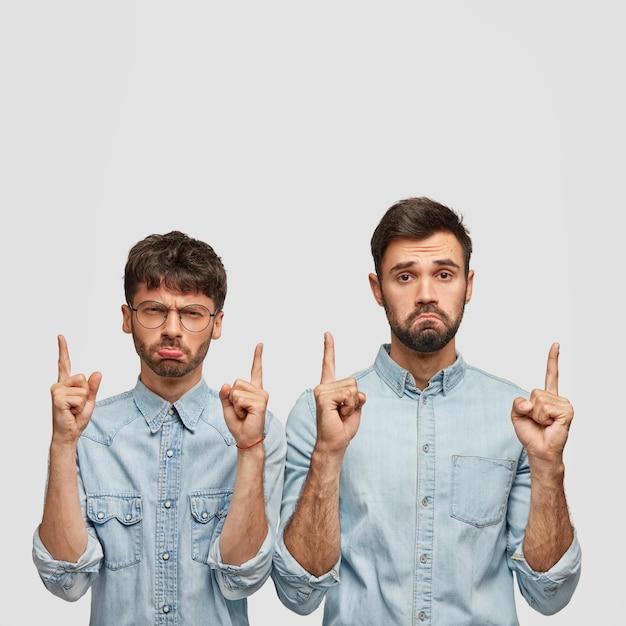 Bärtige zwei männer mit mürrischem gesichtsausdruck, die mit beiden zeigefingern nach oben zeigen und unzufrieden sind