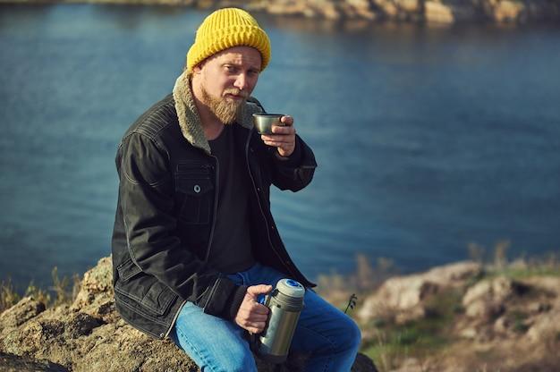 Bärtiger abenteurer mann im gelben hut hält eine metallthermosflasche auf der einen seite und eine tasse tee oder kaffee auf der anderen seite und macht pause beim wandern.