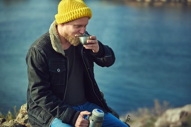 Bärtiger abenteurermann, der eine metallthermosflasche hält und heißes getränk auf see trinkt.
