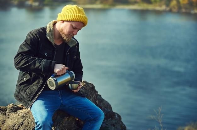 Bärtiger abenteurermann, der tee oder kaffee von der thermoskanne in eine metallschale gießt, während er auf einem felsen auf einem schönen see ruht