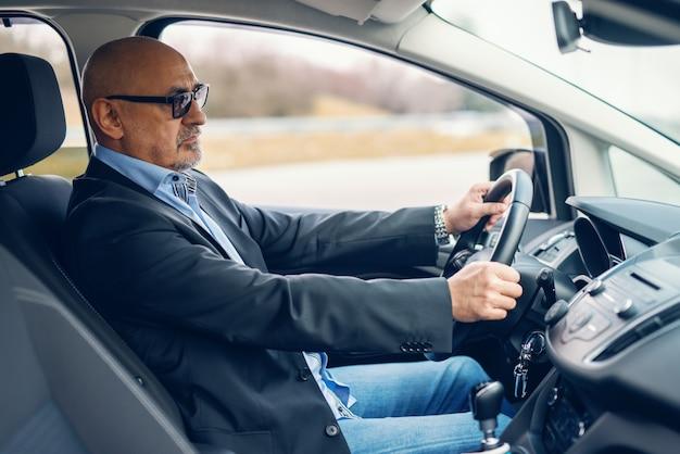 Bärtiger älterer erwachsener geschäftsmann, der auto während des tages fährt. hände auf das lenkrad.