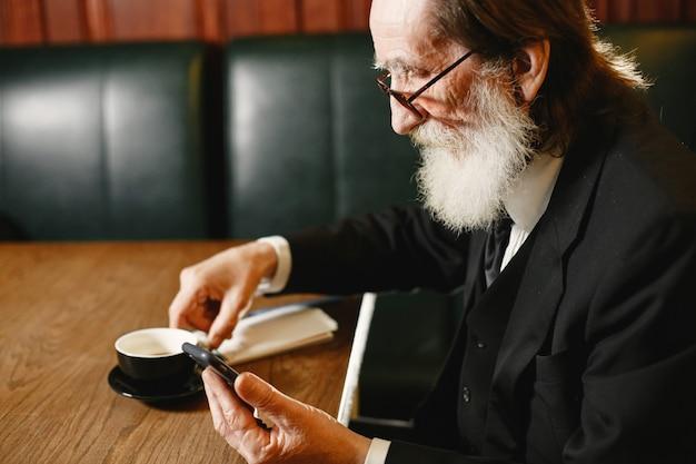 Bärtiger älterer geschäftsmann. mann mit kaffee. senior im schwarzen anzug.