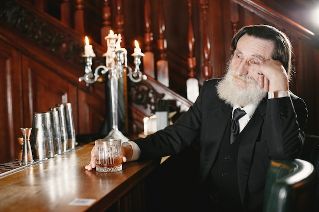 Bärtiger älterer geschäftsmann. mann trinkt einen whisky. senior im schwarzen anzug.