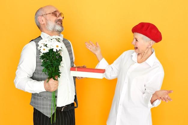 Bärtiger älterer herr mit glatze, der feldblumen und eine schachtel schokoladengeschenk hält, das seiner eleganten freundin mittleren alters am valentinstag geschenkt wird