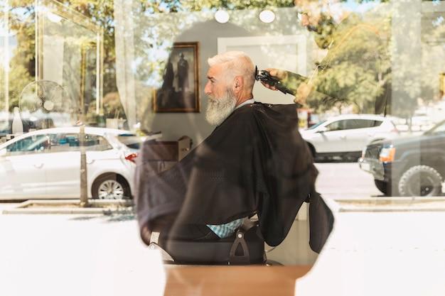 Bärtiger älterer kunde des friseurausschnitt-haarschnitts