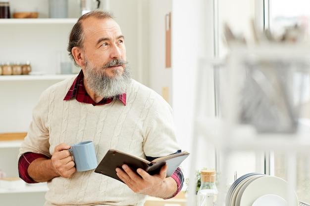 Bärtiger älterer mann, der morgenkaffee genießt