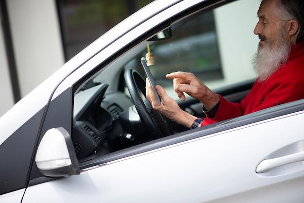 Bärtiger älterer mann, der telefon hält und sms schreibt, während er im auto auf einem parkplatz sitzt