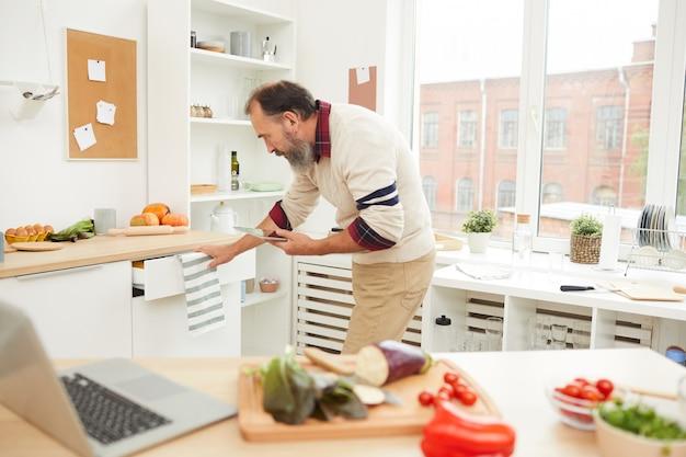 Bärtiger älterer mann in der küche