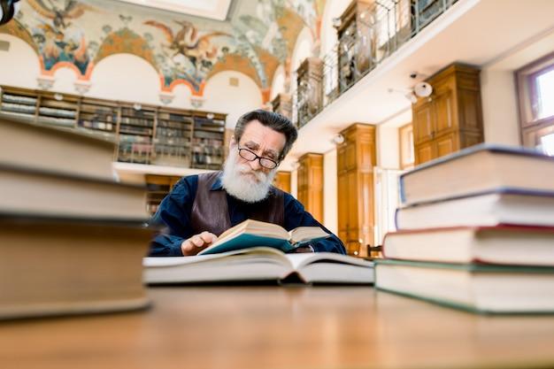 Bärtiger älterer mann, schriftsteller, wissenschaftler, lehrer, buchliebhaber, der in der alten vintage-stadtbibliothek am tisch mit vielen büchern sitzt und ein buch liest