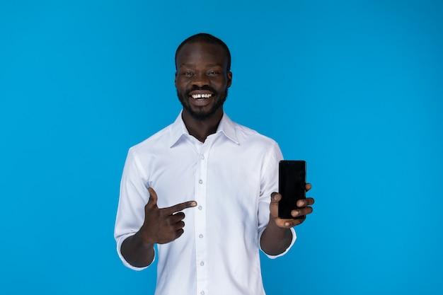 Bärtiger afroamerikanischer kerl zeigt mobiltelefon im weißen hemd