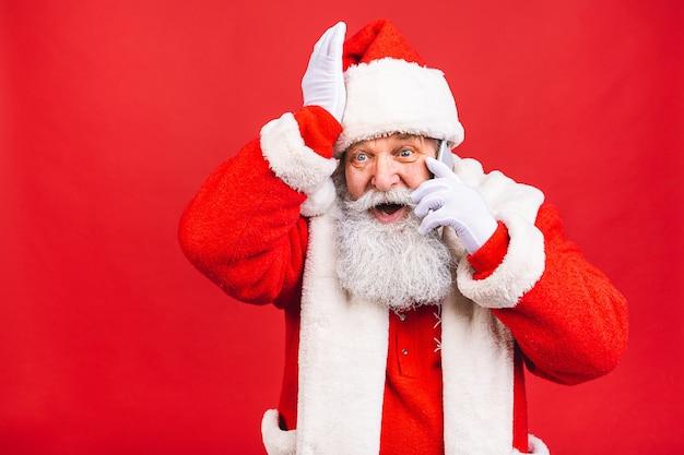 Bärtiger alter mann im weihnachtsmannkostüm, das am telefon steht, das lokal auf rotem hintergrund steht