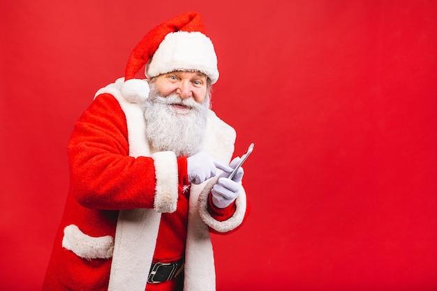 Bärtiger alter mann in santa claus kostüm holdin handy steht isoliert auf rotem hintergrund