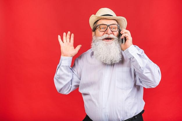 Bärtiger alter mann mit hut und brille, die auf einem handy lokalisiert auf rotem hintergrund sprechen