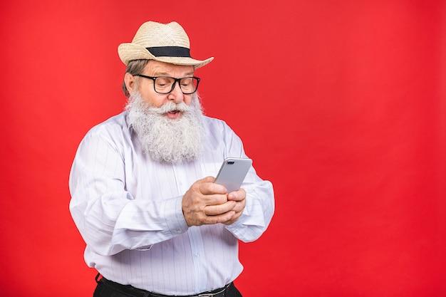 Bärtiger alter mann mit hut und brille, die ein handy lokalisiert auf rotem hintergrund halten