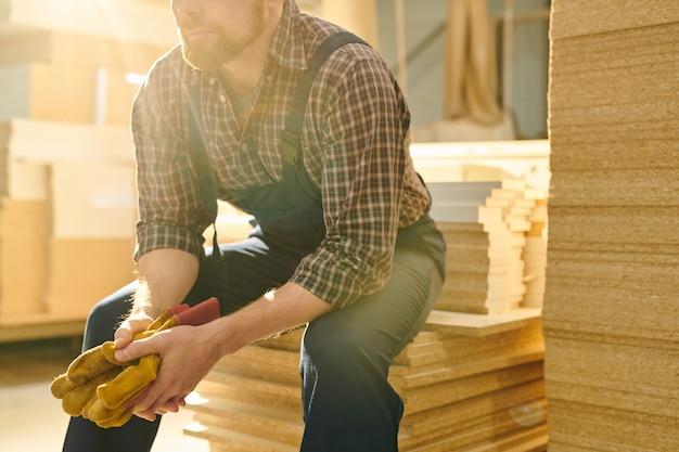 Bärtiger arbeiter sitzt auf stapel von brettern