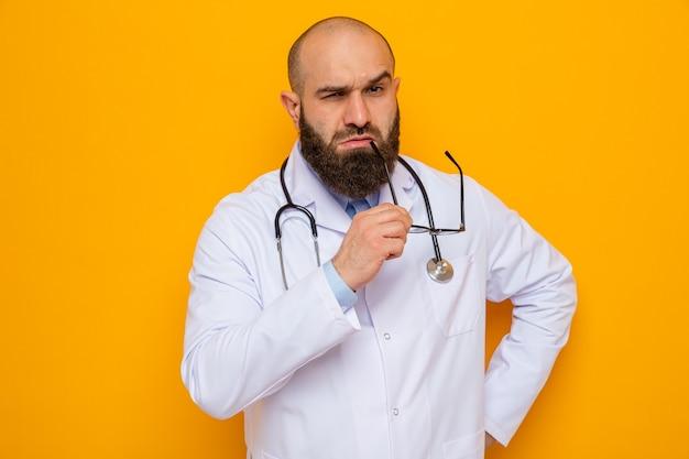 Bärtiger arzt im weißen kittel mit stethoskop um den hals, der eine brille hält und die kamera mit skeptischem ausdruck auf orangefarbenem hintergrund anschaut