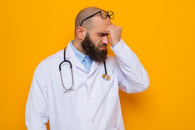 Bärtiger arzt im weißen kittel mit stethoskop um den hals, der eine brille trägt und die faust auf der stirn hält, die verwirrt über orangefarbenem hintergrund aussieht