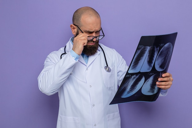 Bärtiger arzt im weißen kittel mit stethoskop um den hals, der eine brille trägt und ein röntgenbild hält, das es eng konzentriert betrachtet