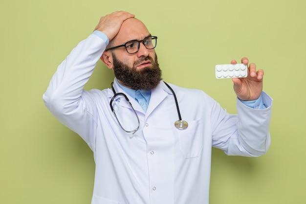 Bärtiger arzt im weißen kittel mit stethoskop um den hals, der eine brille trägt und eine blase mit pillen hält, die sie mit der hand auf dem kopf verwechselt