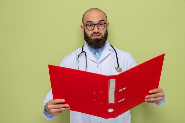 Bärtiger arzt im weißen kittel mit stethoskop um den hals, der eine brille trägt und einen büroordner hält, der die kamera mit ernstem gesicht auf grünem hintergrund anschaut