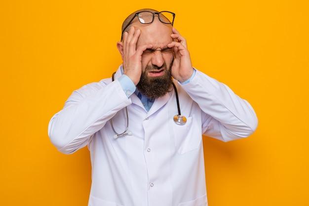 Bärtiger arzt im weißen kittel mit stethoskop um den hals, der eine brille trägt und genervt und erschöpft aussieht