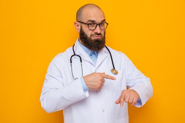 Bärtiger arzt im weißen kittel mit stethoskop um den hals, der eine brille trägt und mit dem finger auf seine hand zeigt, die an die zeit erinnert