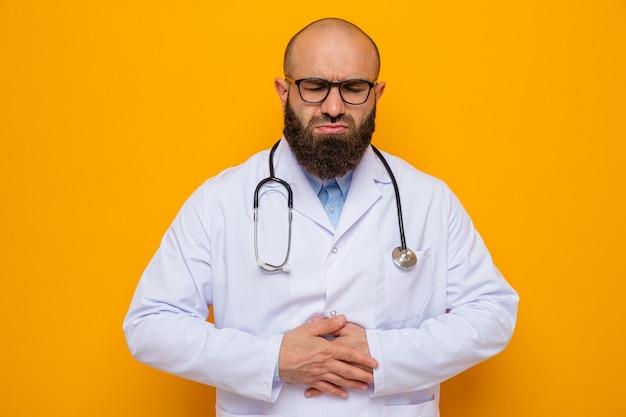 Bärtiger arzt im weißen kittel mit stethoskop um den hals, der eine brille trägt und unwohl aussieht, wenn er seinen bauch berührt und schmerzen fühlt
