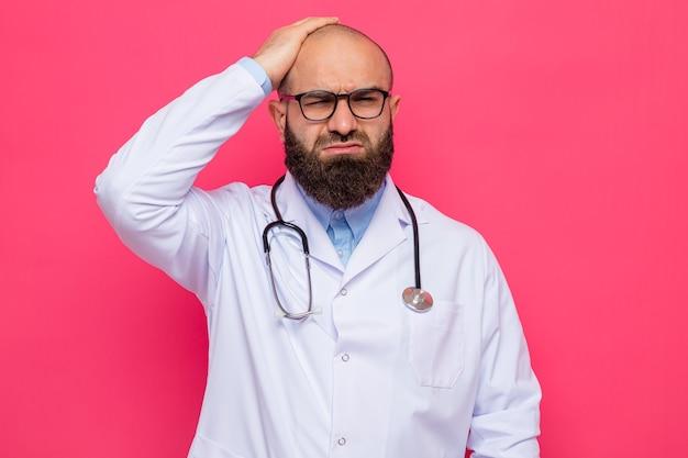Bärtiger arzt im weißen kittel mit stethoskop um den hals, der eine brille trägt und verwirrt aussieht und sehr ängstlich die hand auf dem kopf hält, um einen fehler zu machen