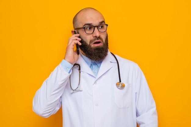 Bärtiger arzt im weißen kittel mit stethoskop um den hals, der eine brille trägt und verwirrt schaut, während er auf dem handy über orangefarbenem hintergrund spricht