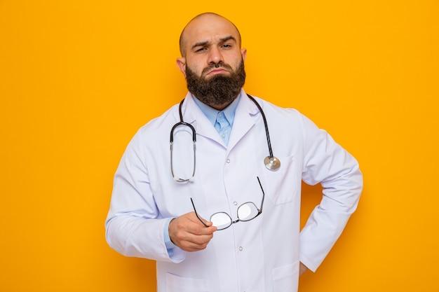 Bärtiger arzt im weißen kittel mit stethoskop um den hals, der mit selbstbewusstem ausdruck in die kamera schaut und eine brille über orangefarbenem hintergrund hält