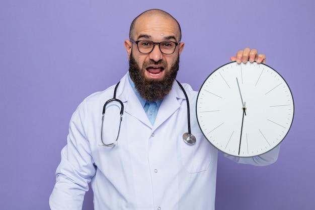 Bärtiger arzt im weißen kittel mit stethoskop um den hals mit brille, der die uhr mit blick auf die kamera glücklich und aufgeregt auf violettem hintergrund hält