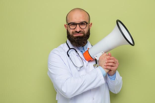 Bärtiger arzt im weißen kittel mit stethoskop um den hals mit brille, der megaphon hält und selbstbewusst lächelt