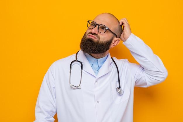 Bärtiger arzt im weißen kittel mit stethoskop um den hals mit brille, der verwirrt aufblickt und sich den kopf kratzt, der über orangefarbenem hintergrund steht
