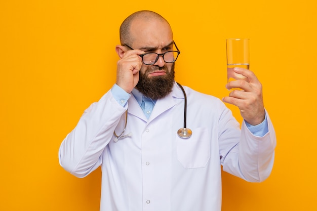 Bärtiger arzt im weißen kittel mit stethoskop um den hals mit brille, die ein glas wasser hält und es eng über orangefarbenem hintergrund betrachtet