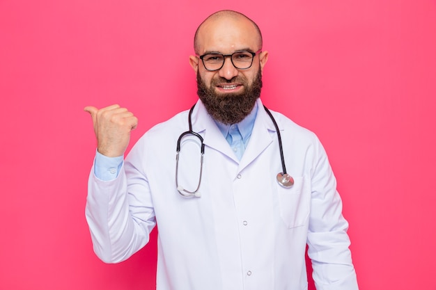 Bärtiger arzt im weißen kittel mit stethoskop um den hals mit brille und blick in die kamera, die fröhlich lächelt und mit dem daumen nach hinten auf rosafarbenem hintergrund zeigt