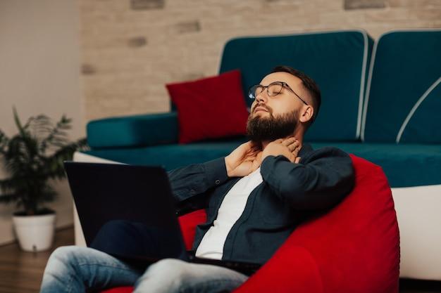 Bärtiger, attraktiver mann in der brille, die zu hause vor laptop-bildschirm entspannt. er hielt hände am hals mit geschlossenen augen, friedliche pause im home office nach dem arbeitstag.