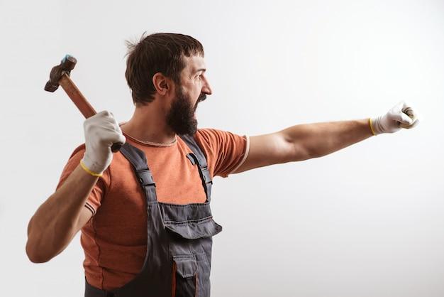 Bärtiger baumeister, der mit hammer arbeitet