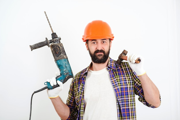 Bärtiger baumeister, der mit hammer und bohrer arbeitet