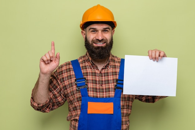Bärtiger baumeister in bauuniform und schutzhelm, der eine leere seite hält, die fröhlich lächelt und den zeigefinger zeigt, der eine neue idee hat
