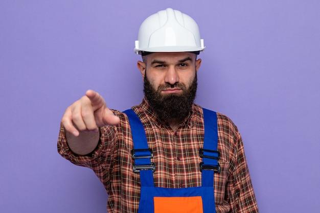 Bärtiger baumeister in bauuniform und schutzhelm, der mit dem zeigefinger auf die kamera zeigt und mit ernstem gesicht auf violettem hintergrund steht