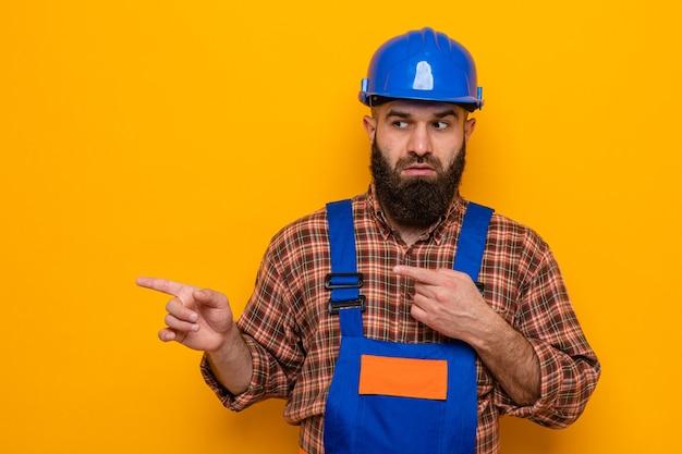 Bärtiger baumeister in bauuniform und schutzhelm, der mit ernstem gesicht beiseite schaut, das mit zeigefingern auf die seite zeigt, die über orangefarbenem hintergrund steht