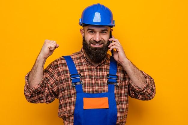 Bärtiger baumeister in bauuniform und schutzhelm glücklich und aufgeregt, die faust lächeln, während er auf dem handy auf orangem hintergrund spricht