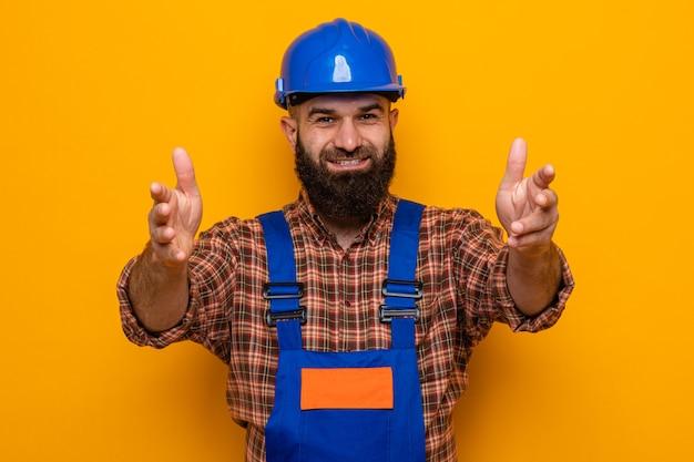 Bärtiger baumeister in bauuniform und schutzhelm mit blick auf die kamera, die fröhlich lächelt und eine einladende geste mit händen auf orangem hintergrund macht