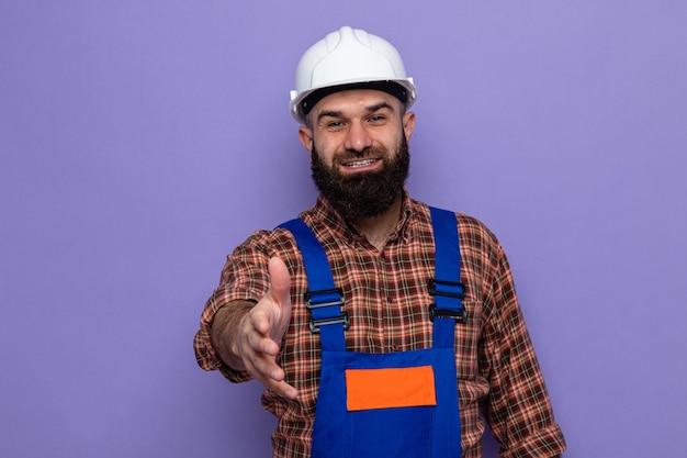 Bärtiger baumeister in bauuniform und schutzhelm mit blick auf die kamera, die fröhlich lächelt und handgrußgeste auf violettem hintergrund anbietet