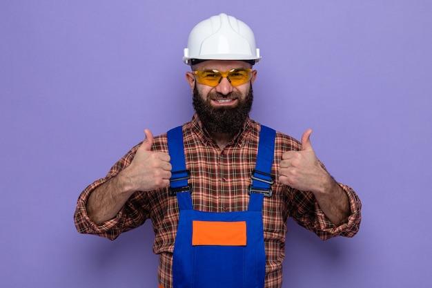 Bärtiger baumeister in bauuniform und schutzhelm mit gelber schutzbrille und blick in die kamera fröhlich lächelnd mit daumen nach oben auf violettem hintergrund