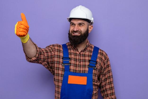 Bärtiger baumeister in bauuniform und schutzhelm mit gummihandschuhen, der beiseite lächelt und fröhlich die daumen zeigt, die über lila hintergrund stehen