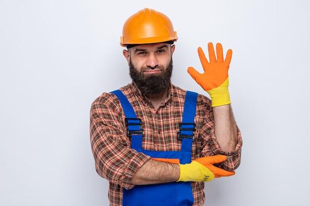 Bärtiger baumeister in bauuniform und schutzhelm mit gummihandschuhen, der die kamera anschaut und selbstbewusst lächelt, fünfter mit handfläche auf weißem hintergrund stehend