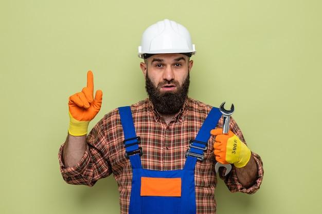 Bärtiger baumeister in bauuniform und schutzhelm mit gummihandschuhen, der einen schraubenschlüssel hält und überrascht mit dem zeigefinger zur seite zeigt