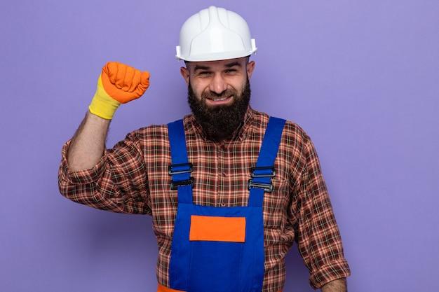 Bärtiger baumeister in bauuniform und schutzhelm mit gummihandschuhen, der glücklich und selbstbewusst in die kamera schaut und die faust wie ein gewinner auf violettem hintergrund hebt