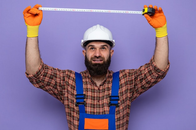 Bärtiger baumeister in bauuniform und schutzhelm mit gummihandschuhen, der mit selbstbewusstem ausdruck aufschaut, der mit maßband auf violettem hintergrund arbeitet